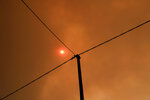 The sun is seen through smoke from a forest fire at Psachna village on the island of Evia, northeast of Athens, Tuesday, Aug. 13, 2019. Dozens of firefighters backed by water-dropping aircraft are battling a wildfire on an island north of Athens that has left the Greek capital blanketed in smoke. (AP Photo/Yorgos Karahalis)