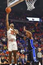 Clemson's Aamir Simms, left, shoots while defended by Duke's Vernon Carey Jr. during the first half of an NCAA college basketball game Tuesday, Jan. 14, 2020, in Clemson, S.C. (AP Photo/Richard Shiro)