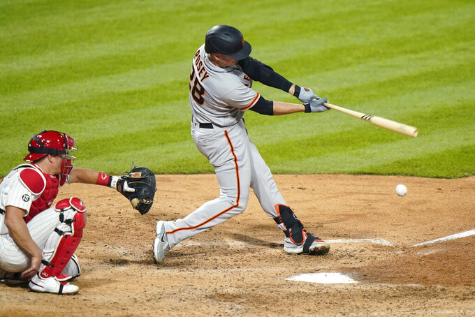 San Francisco Giants' Buster Posey, right, hits a single off Philadelphia Phillies pitcher Connor Brogdon during the eighth inning of a baseball game, Tuesday, April 20, 2021, in Philadelphia. (AP Photo/Matt Slocum)
