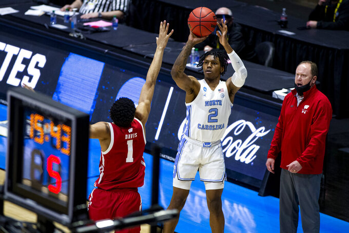 North Carolina's Caleb Love (2) shoots a three-point basket over Wisconsin's Jonathan Davis (1) during the first half of a first-round game in the NCAA men's college basketball tournament, Friday, March 19, 2021, at Mackey Arena in West Lafayette, Ind. (AP Photo/Robert Franklin)