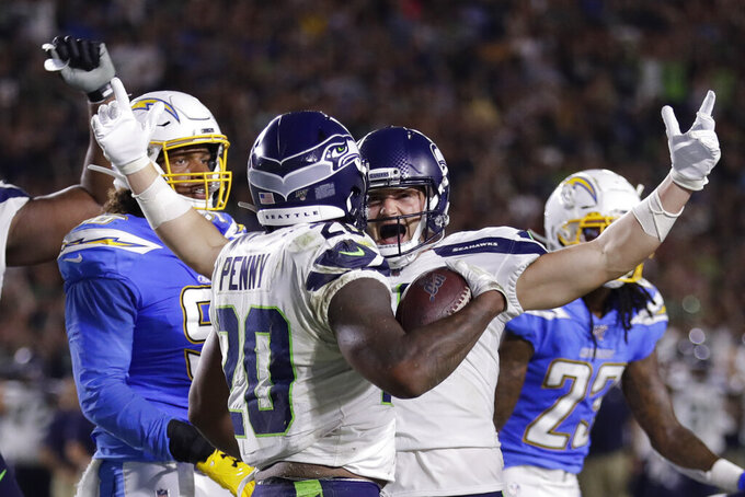 Seattle Seahawks running back Rashaad Penny celebrates his touchdown with Jackson Harris against the Los Angeles Chargers during the first half of an NFL preseason football game Saturday, Aug. 24, 2019, in Carson, Calif. (AP Photo/Gregory Bull)