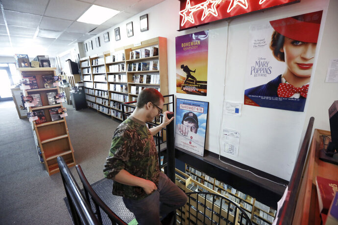 Lewis Peterson, co-owner of Four Star Video Cooperative, makes his way down the spiral staircase where more of the store's inventory is kept on State Street in Madison, Wis., Monday, Aug. 19, 2019. (Amber Arnold/Wisconsin State Journal via AP)