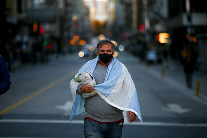 A man arrives to a protest against how the government of President Alberto Fernandez is handling the new coronavirus pandemic crisis in Buenos Aires, Argentina, Tuesday, May 25, 2021. (AP Photo/Marcos Brindicci)