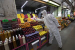 A health worker in protection gear as a measure to curb the spread of the new coronavirus, gives alcohol to a vendor to disinfect her hands at the Central de Abasto market in Mexico City, Thursday, June 18, 2020. The passageways at the market have remained crowded despite the pandemic. (AP Photo/Marco Ugarte)