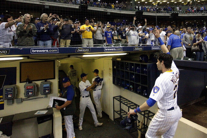 "FILE - In this Sept. 7, 2019, file photo, fans cheer as Milwaukee Brewers' Christian Yelich walks off the field after driving in the winning run with a double during the ninth inning of the team's baseball game against the Chicago Cubs in Milwaukee. Major League Baseball will start each extra inning this season by putting a runner on second base. This rule has been used since 2018 in the minor leagues, where it created more action and settled games sooner. ""I think it's great,"" Yelich said. ""As a player, there's nothing worse than extra innings."" (AP Photo/Aaron Gash, File)"