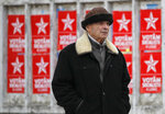 A man walks by electoral posters advertising the candidates of the Socialists' Party, in Chisinau, Moldova, Thursday, Feb. 21, 2019, ahead of parliamentary elections taking place on Feb. 24. Moldova's president says the former Soviet republic needs good relations with Russia, amid uncertainty about the future of the European Union.(AP Photo/Vadim Ghirda)