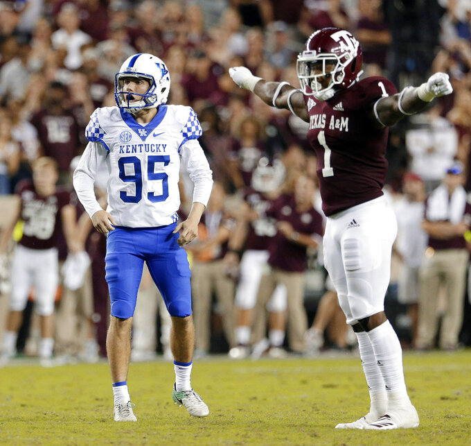Kentucky place kicker Miles Butler (95) reacts after missing a 3-point attempt as Texas A&M linebacker Buddy Johnson (1) signals no score in overtime of an NCAA college football game Saturday, Oct. 6, 2018, in College Station, Texas. (AP Photo/Michael Wyke)