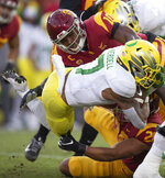 Southern California linebacker John Houston Jr., top, and linebacker Kana'i Mauga tackle Oregon running back CJ Verdell during the first half of an NCAA college football game Saturday, Nov. 2, 2019, in Los Angeles. (AP Photo/Kyusung Gong)