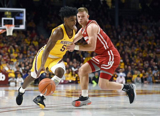 Minnesota's Marcus Carr (5) drives next to Wisconsin's Brad Davison during the first half of an NCAA college basketball game Wednesday, Feb. 5, 2020, in Minneapolis. (AP Photo/Hannah Foslien)