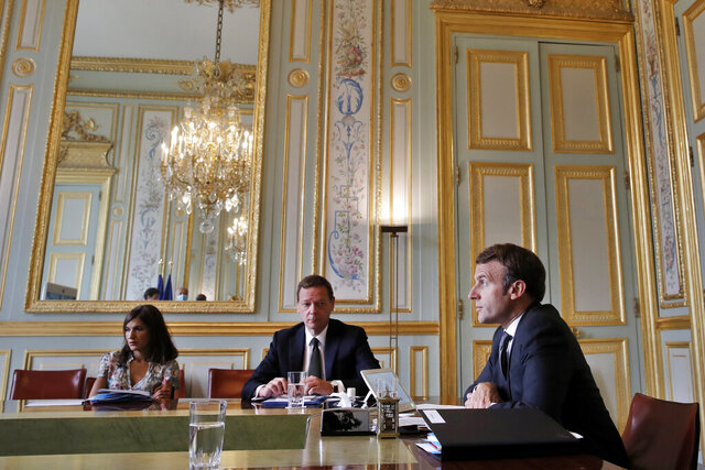 France's President Emmanuel Macron, right, attends a visio conference with Kosovo Prime Minister Avdullah Hoti, Serbian President Aleksandar Vucic, and German Chancellor Angela Merkel, at the Elysee Palace, in Paris, Friday, July 10, 2020. The leaders of Serbia and Kosovo will hold talks in Brussels on July 12, the first meeting between the two in long-stalled European Union-supervised negotiations aimed at normalizing relations, European Commission spokesman Peter Stano said Monday. (AP Photo/Christophe Ena, Pool)