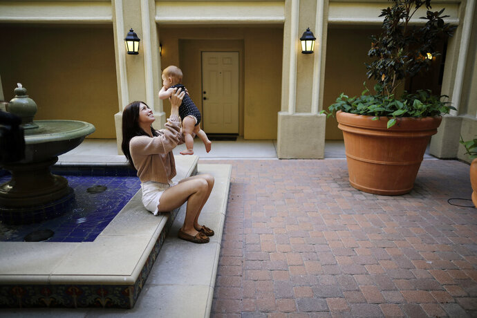 FILE - In this Aug. 24, 2018 file photo Keira Sumimoto plays with her daughter, in Irvine, Calif. Sumimoto, who used marijuana briefly for medical reasons while pregnant and breastfeeding, says her daughter is healthy and advanced for her age. More than three years after California voters approved broad legalized marijuana, a state panel is considering if the potent high-inducing chemical THC found in pot should be declared a risk to pregnant women and require warnings to consumers. (AP Photo/Gregory Bull,File)