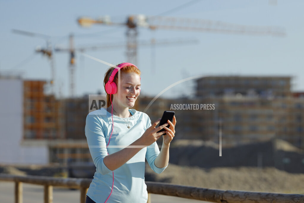 Woman using mobile phone while listening music