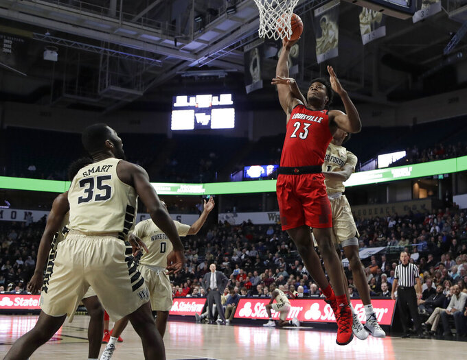 Louisville's Steven Enoch (23) is fouled as he drives to the basket against Wake Forest's Isaiah Mucius (1) during the first half of an NCAA college basketball game in Winston-Salem, N.C., Wednesday, Jan. 30, 2019. (AP Photo/Chuck Burton)
