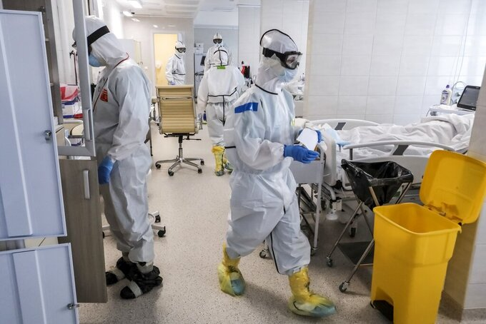 In this photo taken on Saturday, May 2, 2020, doctors work inside the intensive care unit for people infected with the new coronavirus, at a hospital in Moscow, Russia. A Russian epidemiologist says the sharp increase in coronavirus infection cases recorded over the past week reflects increased testing. Russia on Sunday reported more then ten thousand new cases, nearly double the new cases reported a week ago and the first time the daily tally went into five digits.(AP Photo/Sophia Sandurskaya)