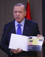 Turkish President Recep Tayyip Erdogan shows a document with a map of Turkey-Syria border as he speaks to reporters before a visit to the United States, in Ankara, Turkey, Tuesday, Nov. 12, 2019. Erdogan warned European nations Tuesday that his country could release all the Islamic State group prisoners it holds and send them to Europe, in response to EU sanctions over Cyprus.(Presidential Press Service via AP, Pool)