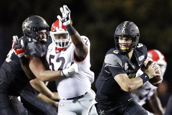 Vanderbilt quarterback Riley Neal (6) scrambles away from Georgia defensive lineman Tyler Clark (52) in the first half of an NCAA college football game Saturday, Aug. 31, 2019, in Nashville, Tenn. (AP Photo/Mark Humphrey)