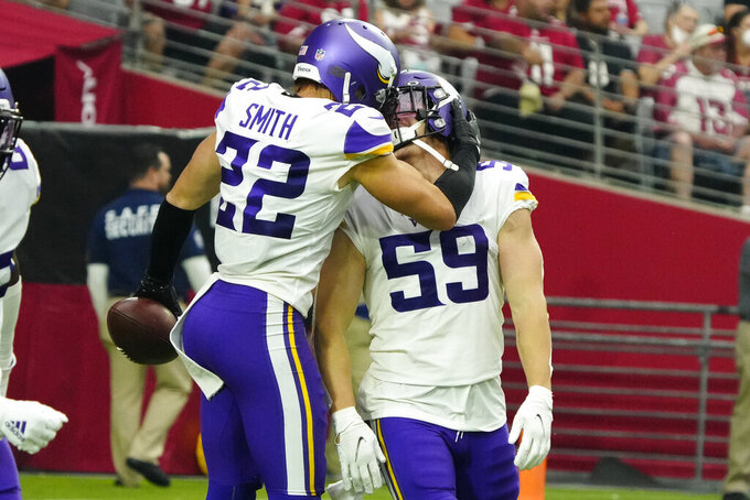 Minnesota Vikings outside linebacker Nick Vigil (59) celebrates his interception for a touchdown with free safety Harrison Smith (22) during the second half of an NFL football game against the Arizona Cardinals, Sunday, Sept. 19, 2021, in Glendale, Ariz. (AP Photo/Rick Scuteri)