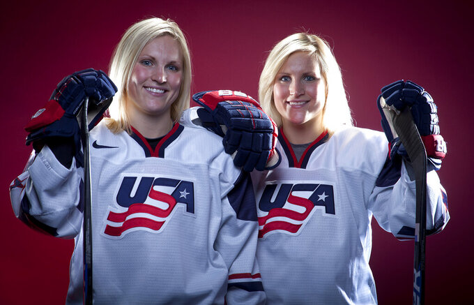 FILE - In this Oct. 2, 2013, file photo, United States Olympic Winter Games hockey players Jocelyne Lamoureux, left, and Monique Lamoureux pose for a portrait at the Team USA Media Summit in Park City, Utah. USA Hockey's twin-sister Lamoureux tandem is retiring after 14 years of international competition. Jocelyne Lamoureux-Davidson and Monique Lamoureux-Morando made the joint announcement in an article published on The Players' Tribune on Tuesday, Feb. 9, 2021.  (AP Photo/Carlo Allegri, File)