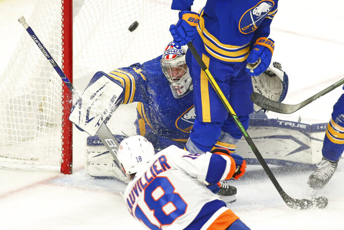 Buffalo Sabres goalie Michael Houser (32) stops New York Islanders forward Anthony Beauvollier (18) during the first period of an NHL hockey game, Monday, May 3, 2021, in Buffalo, N.Y. (AP Photo/Jeffrey T. Barnes)