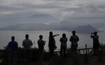People look at Taal volcano in Tagaytay, Cavite province, southern Philippines on Friday Jan. 17, 2020. Taal volcano remains life-threatening despite weaker emissions and fewer tremors, an official said Friday and advised thousands of displaced villagers not to return to the danger zone. (AP Photo/Aaron Favila)