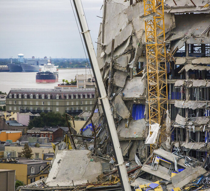 A ship floats on the Mississippi River by the Hard Rock Hotel construction site in New Orleans, Friday, Oct. 18, 2019. The Hard Rock Hotel partially collapsed last week. (Sophia Germer/The Advocate via AP)