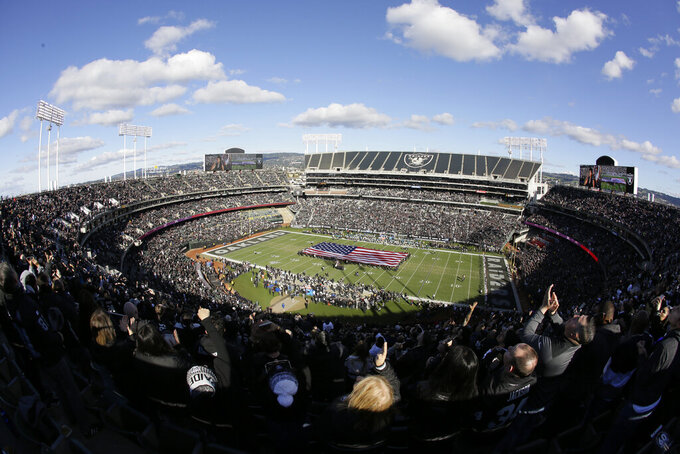 Fans stand for the National Anthem and flyover before an NFL football game between the Oakland Raiders and the Jacksonville Jaguars in Oakland, Calif., Sunday, Dec. 15, 2019. The game is the final scheduled Raiders game in Oakland. (AP Photo/Eric Risberg)