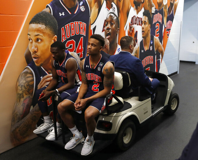 Auburn's Jared Harper (1) and Bryce Brown (2) ride a cart back to the locker room after the team's 63-62 loss to Virginia in the semifinals of the Final Four NCAA college basketball tournament, Saturday, April 6, 2019, in Minneapolis. (AP Photo/Jeff Roberson)