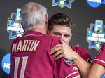 Florida State coach Mike Martin hugs Mike Salvatore, right, during a news conference after the team's 4-1 loss to Texas Tech in a College World Series elimination baseball game Wednesday, June 19, 2019, in Omaha, Neb. It was Martin's final game. (Chris Machian/Omaha World-Herald via AP)
