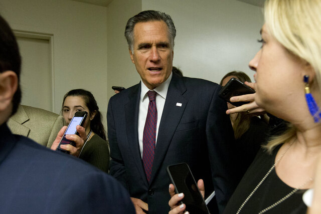 Sen. Mitt Romney, R-Utah, talks to reporters as he walks to attend the impeachment trial of President Donald Trump on charges of abuse of power and obstruction of Congress, Tuesday, Jan. 28, 2020, on Capitol Hill in Washington. (AP Photo/Jose Luis Magana)
