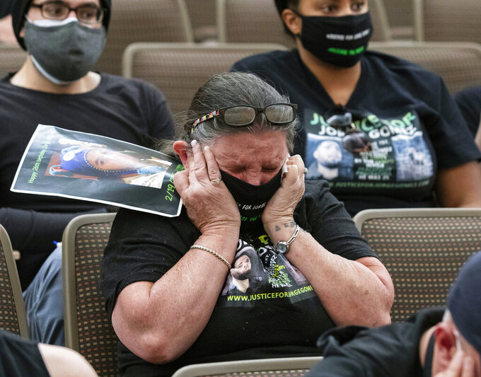 Carol Luke blocks her ears as video of Jorge Gomez's shooting is played during a public fact-finding review for the fatal officer involved shooting of Gomez at the Clark County Government Center, on Friday, April 16, 2021, in Las Vegas. (Bizuayehu Tesfaye/Las Vegas Review-Journal via AP)