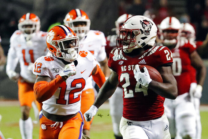 North Carolina State's Zonovan Knight (24) runs away from Clemson's K'Von Wallace (12) for a touchdown during the second half of an NCAA college football game in Raleigh, N.C., Saturday, Nov. 9, 2019. (AP Photo/Karl B DeBlaker)