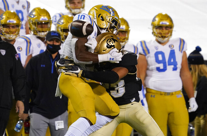 Colorado safety Isaiah Lewis, front right, hits UCLA running back Demetric Felton who loses control of the ball for an incomplete pass in the first half of an NCAA college football game Saturday, Nov. 7, 2020, in Boulder, Colo. (AP Photo/David Zalubowski)