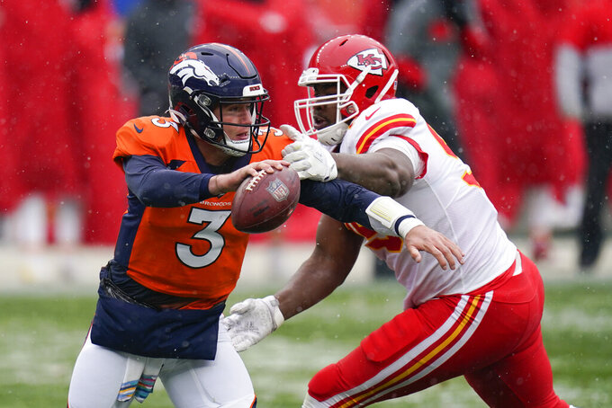Denver Broncos quarterback Drew Lock scrambles under pressure from Kansas City Chiefs defensive tackle Chris Jones during the first half of an NFL football game Sunday, Oct. 25, 2020, in Denver. (AP Photo/Jack Dempsey)