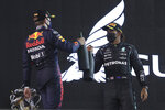 Winner, Mercedes driver Lewis Hamilton of Britain, right, celebrates with Red Bull driver Max Verstappen of the Netherlands, second place, on the podium after the Bahrain Formula One Grand Prix at the Bahrain International Circuit in Sakhir, Bahrain, Sunday, March 28, 2021. (AP Photo/Kamran Jebreili)