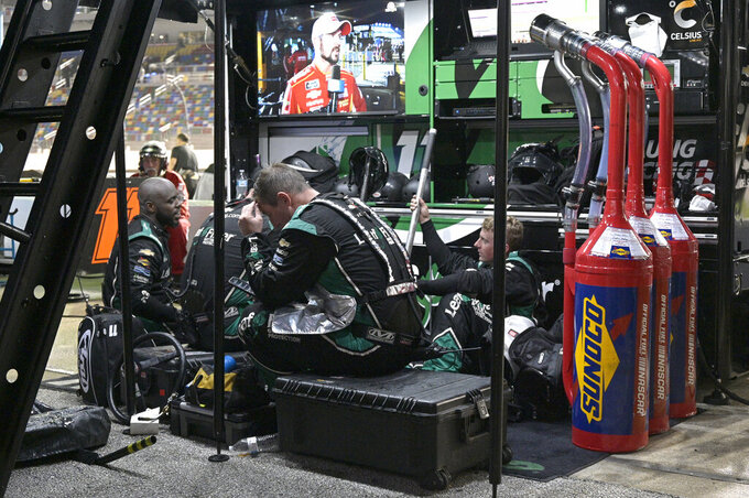 Crew members for Justin Haley's team sit under cover from the rain during a delay in a NASCAR Xfinity Series auto race at Daytona International Speedway, Friday, Aug. 27, 2021, in Daytona Beach, Fla. (AP Photo/Phelan M. Ebenhack)