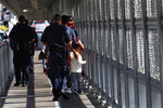 United States Customs and Border Protection Officers escort migrants being taken to apply for asylum in the United States, on the International Bridge 1 in Nuevo Laredo, Mexico, Wednesday, July 17, 2019. Asylum-seekers grappled to understand what a new U.S. policy that all but eliminates refugee claims by Central Americans and many others meant for their bids to find a better life in America amid a chaos of rumors, confusion and fear. (AP Photo/Marco Ugarte)