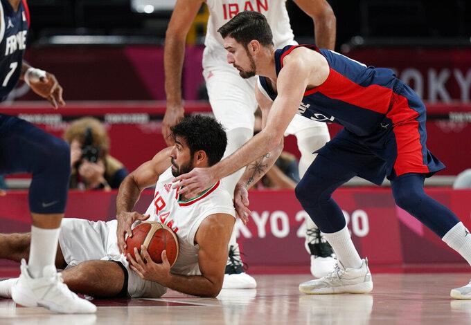 Iran's Arsalan Kazemi (41), left, and France's Nando de Colo (12) scramble for a loose ball during men's basketball preliminary round game at the 2020 Summer Olympics, Saturday, July 31, 2021, in Saitama, Japan. (AP Photo/Eric Gay)