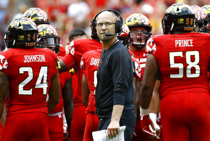 Maryland interim head coach Matt Canada, center, huddles with the team during the first half of an NCAA college football game against Texas, Saturday, Sept. 1, 2018, in Landover, Md. (AP Photo/Patrick Semansky)