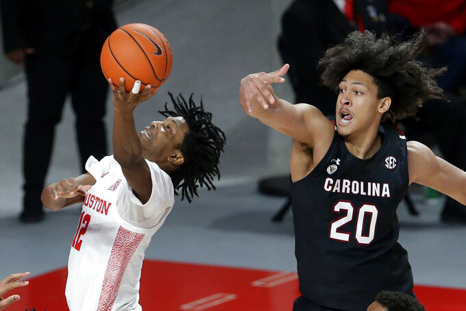 Houston guard Tramon Mark (12) shoots next to South Carolina forward Alanzo Frink (20) during the second half of an NCAA college basketball game Saturday, Dec. 5, 2020, in Houston. (AP Photo/Michael Wyke)