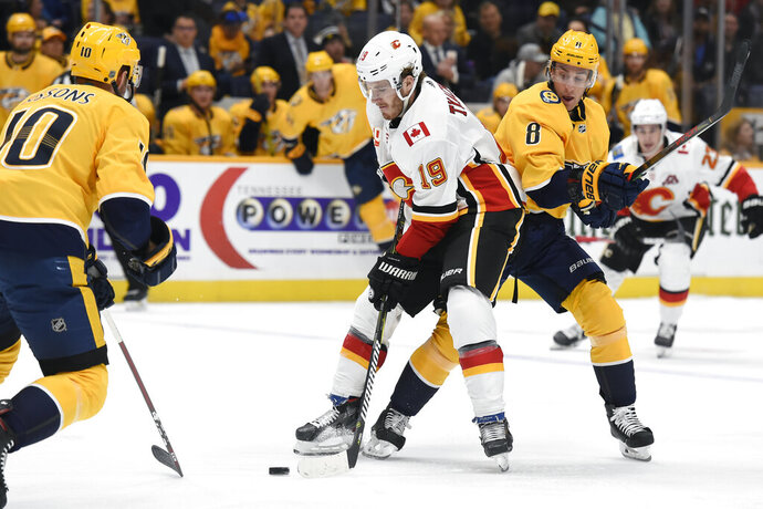 Calgary Flames left wing Matthew Tkachuk (19) moves the puck between Nashville Predators center Colton Sissons (10) and Kyle Turris (8) during the first period of an NHL hockey game Thursday, Oct. 31, 2019, in Nashville, Tenn. (AP Photo/Mark Zaleski)