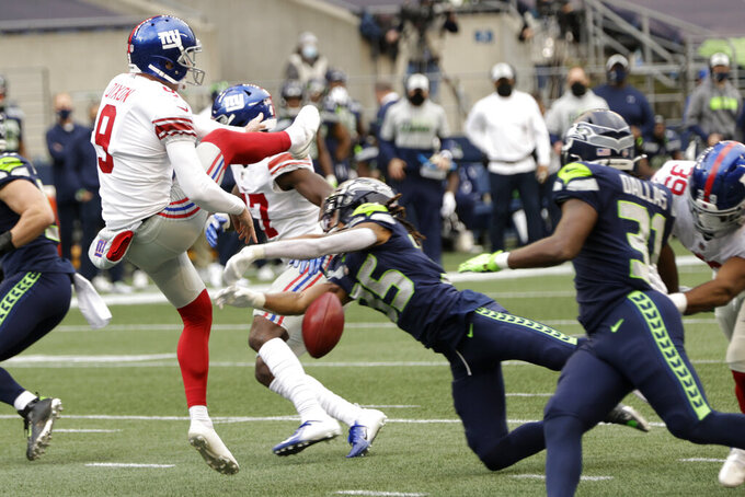 New York Giants punter Riley Dixon has a punt blocked by Seattle Seahawks cornerback Ryan Neal, center, for a safety during the first half of an NFL football game, Sunday, Dec. 6, 2020, in Seattle. (AP Photo/Larry Maurer)