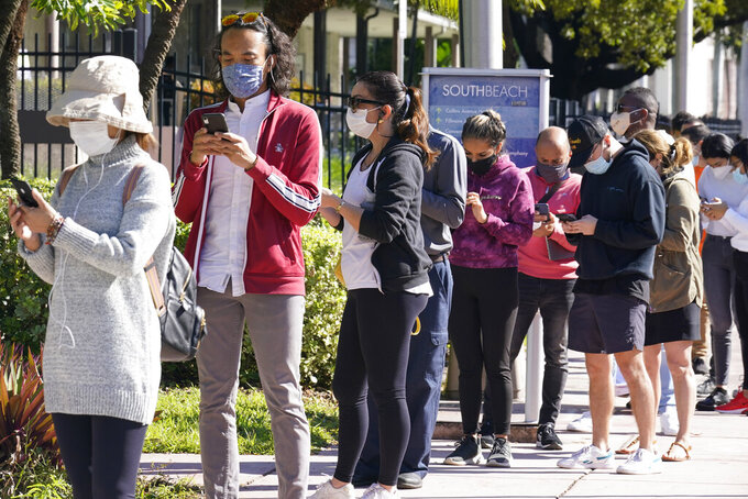 People wait in line to be tested for COVID-19, Tuesday, Dec. 1, 2020, in Miami Beach, Fla. (AP Photo/Marta Lavandier
