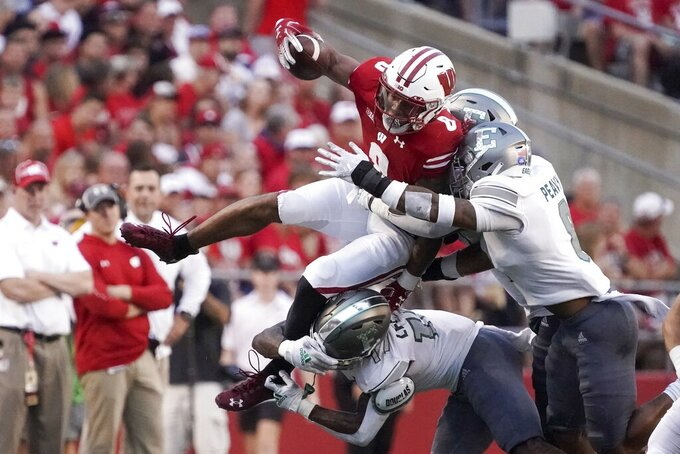 Wisconsin's Jalen Berger is stopped by Eastern Michigan's T.J. Peavy and Mark Lee Jr.during the first half of an NCAA college football game Saturday, Sept. 11, 2021, in Madison, Wis. (AP Photo/Morry Gash)