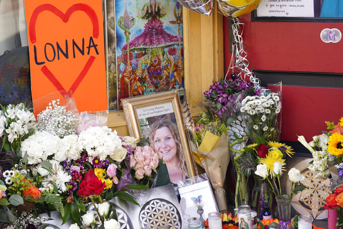 A tribute is displayed outside the store owned by one of 10 victims in the mass shooting at a King Soopers grocery store in Boulder, Colo., Wednesday, March 24, 2021, in Boulder, Colo. A shrine filled with candles and flowers kept growing Wednesday outside Umba Love, the clothing and accessories shop that victim Tralona Bartkowiak ran with her sister on Boulder's popular Pearl Street Mall. Bartkowiak died in the supermarket shooting attack on Monday. (AP Photo/David Zalubowski)