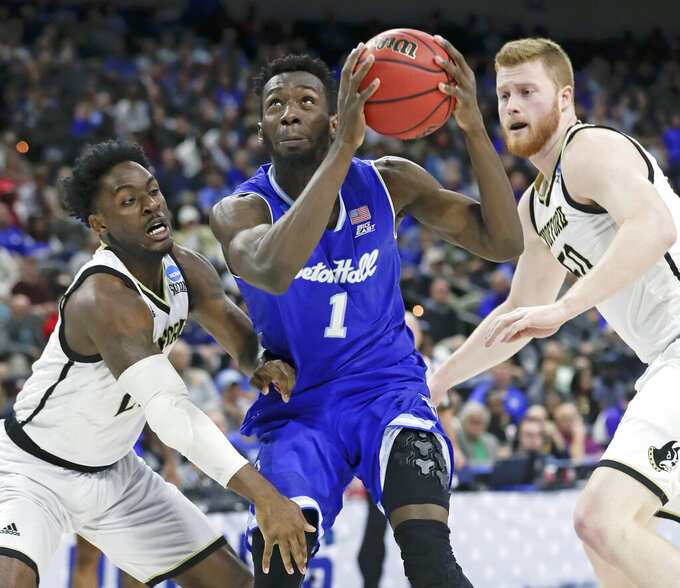 Seton Hall's Michael Nzei (1) looks for a shot as he gets between Wofford's Tray Hollowell, left, and Matthew Pegram during the first half of a first-round game in the NCAA men's college basketball tournament in Jacksonville, Fla., Thursday, March 21, 2019. (AP Photo/John Raoux)