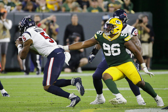 Green Bay Packers defensive tackle Kingsley Keke (96) reaches to grab Houston Texans quarterback Joe Webb during the second half of an NFL preseason football game Thursday, Aug. 8, 2019, in Green Bay, Wis. (AP Photo/Mike Roemer)