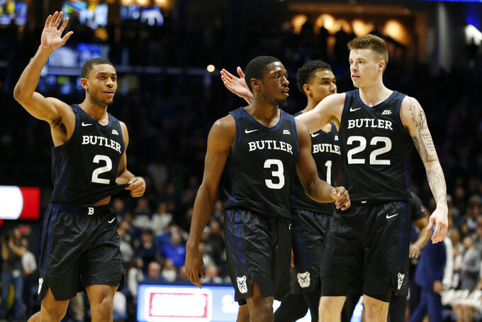 Butler's Aaron Thompson (2), Kamar Baldwin (3), and Sean McDermott (22) celebrate in the final seconds of the team's win over Xavier in an NCAA college basketball game, Saturday, March 7, 2020, in Cincinnati. (AP Photo/Gary Landers)