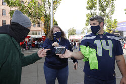 A stadium worker, left, checks for proof of vaccine against COVID-19 as fans prepare to enter Lumen Field before an NFL football game between the Seattle Seahawks and the Tennessee Titans, Sunday, Sept. 19, 2021, in Seattle. (AP Photo/John Froschauer)