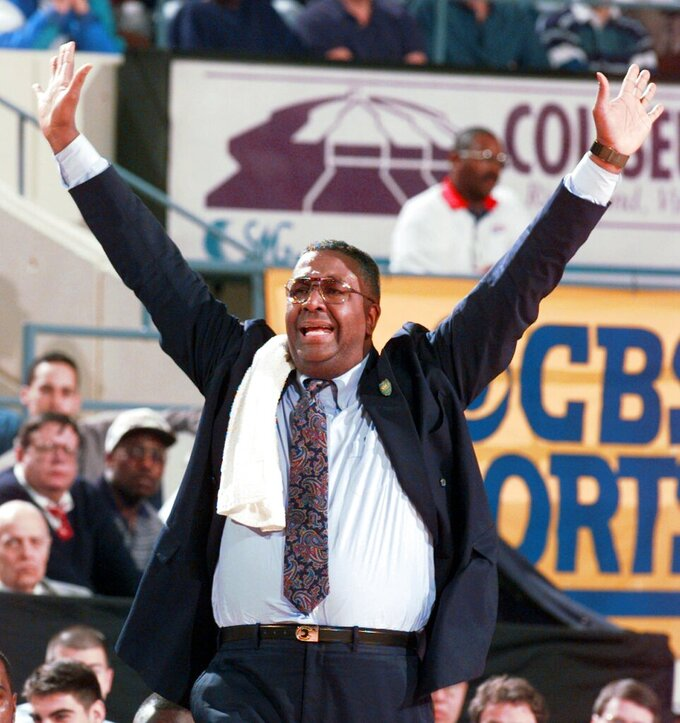 "FILE - In this March 15, 1996, file photo, Georgetown head coach John Thompson yells to his players during the second half of a first round NCAA college basketball game at the Richmond Coliseum in Richmond, Va. John Thompson, the imposing Hall of Famer who turned Georgetown into a ""Hoya Paranoia"" powerhouse and became the first Black coach to lead a team to the NCAA men's basketball championship, has died. He was 78 His death was announced in a family statement Monday., Aug. 31, 2020. No details were disclosed. (AP Photo/Doug Mills, File)"