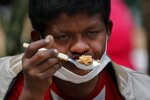 Wearing a mask to curb the spread of the new coronavirus, Delio Carballo Martinez, who is unemployed, eats